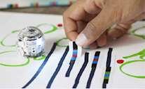 Bild på en hand som ritar en bana för roboten Ozobot.
